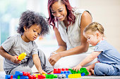 A teacher is sitting on the floor with two preschool children - they are playing with colorful lego blocks.