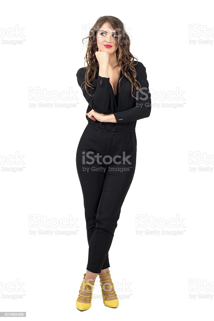 Daydreaming brunette beauty in black overalls looking up stock photo
