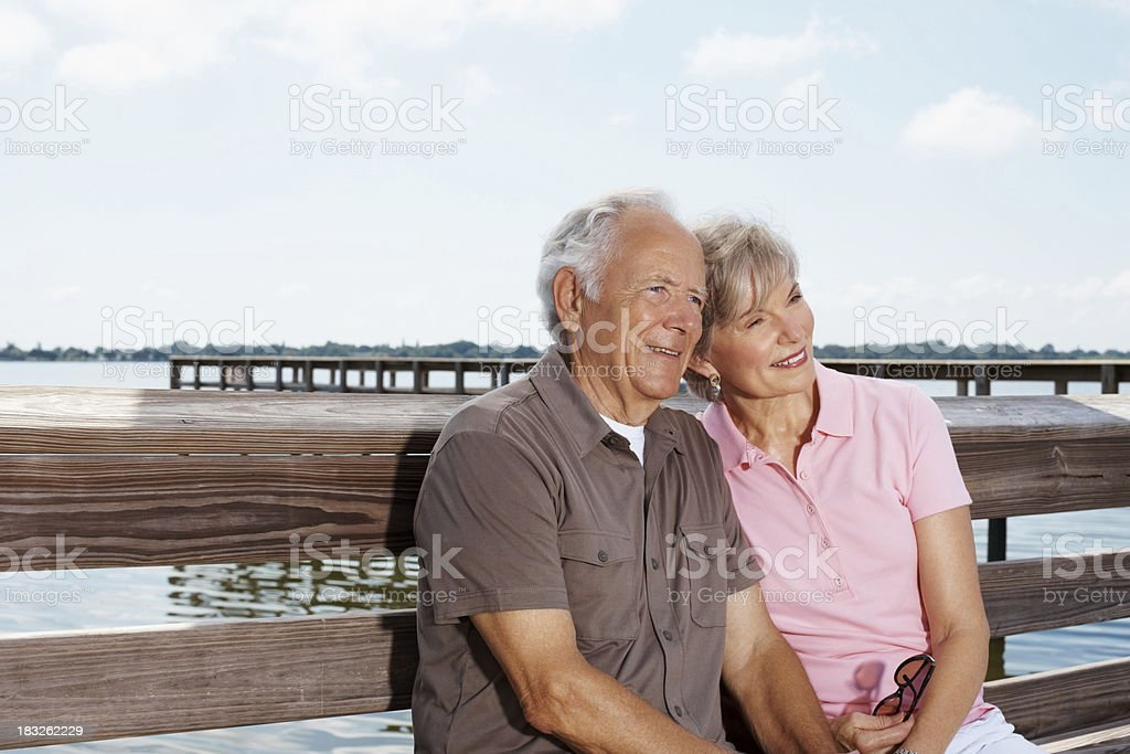 Daydreaming - Happy mature couple sitting together and looking away royalty-free stock photo
