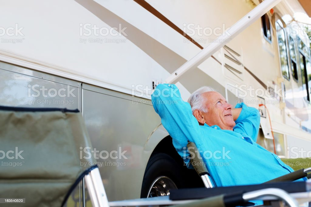 Daydreaming - Mature man sitting by a caravan royalty-free stock photo