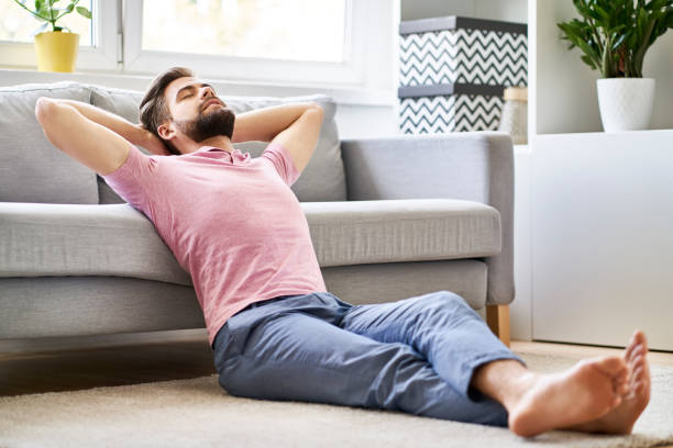 Daydreaming, relaxed man sitting on the floor at living room stock photo