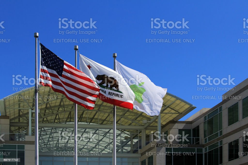 Daylight photo of the three flags at the main entrance of Apple stock photo