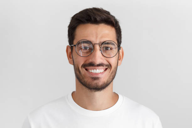 Daylight portrait of young handsome caucasian man isolated on grey background, dressed in white t-shirt and round eyeglasses, looking at camera and smiling positively stock photo