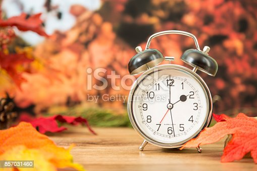 It's daylight savings time.  The alarm clock is set for 2 o'clock am on an outdoor table with autumn trees, leaves in background.  Copyspace at side.