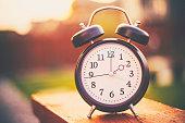 istock Daylight savings time. Retro clock outdoors with warm glow 926055184