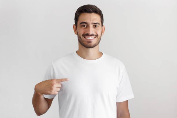 회색 바탕에 검지 손가락, 귀하의 광고에 대 한 복사 공간으로 그의 공백 백색 t-셔츠에서 가리키는 웃는 젊은 남자의 일광 총 고립 - 백인종 뉴스 사진 이미지
