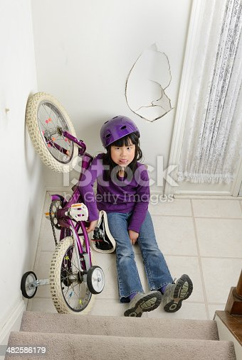 A dazed young girl sits next to her upside-down bike at the bottom of her house's stairs, a damaged wall behind her