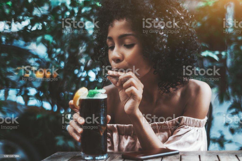 Schillernde biracial Mädchen trinkt einen cocktail im freien – Foto