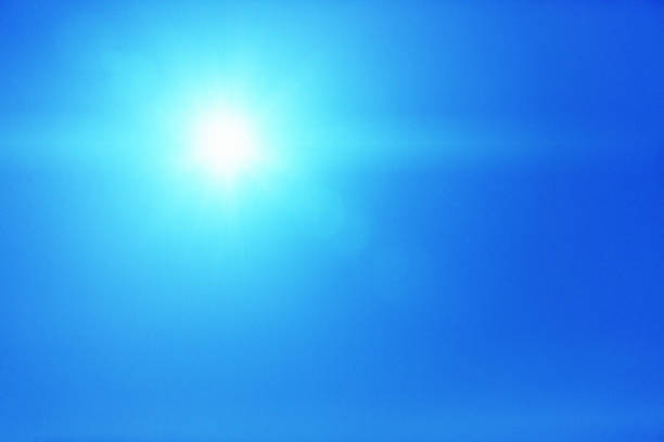 Dazzling bright sun shines in a clear blue sky Hot sun beats down from a clear sky. dazzled stock pictures, royalty-free photos & images