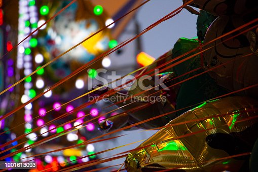 Intersection of circles of light with mixed shades of red and blue and degrees of transparency, from the lights of a fairground ride. The balloons in the foreground strain to the side, held in place by strings.