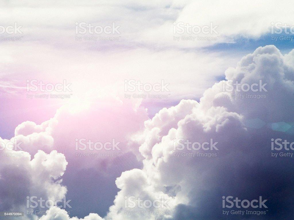 Dazzling sun shining from behind towering cumulonimbus clouds stock photo