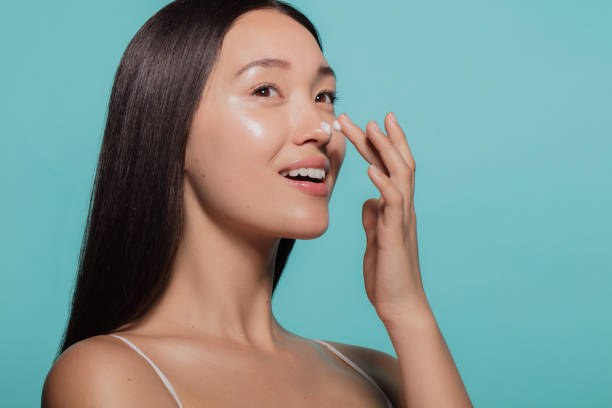 Dazzling woman applying moisturizing cream Close up of female model applying moisturizer cream to her nose. Woman applying moisturizer cream on her face against blue background. korean ethnicity stock pictures, royalty-free photos & images