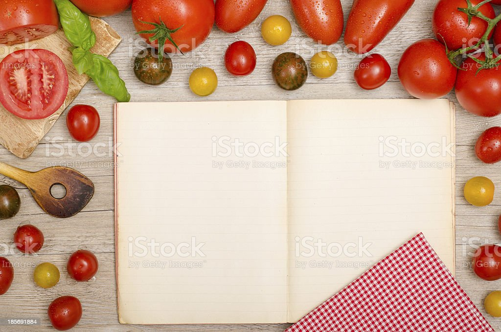 dDifferent tomatoes, basil, wooden spoon and a book royalty-free stock photo
