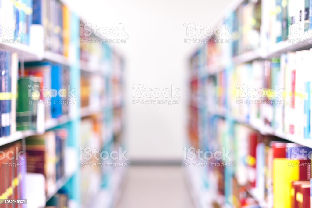 De focused/ Blurred image of books on the bookshelves in library. stock photo