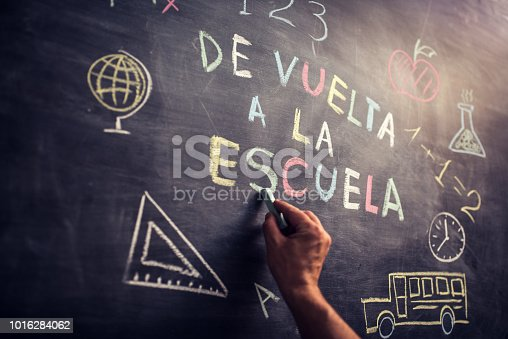 """Hand writing """"De vuelta a la escuela"""" multicoloured words blackboard (Back to School in spanish language . She is also drawing a school bus, an apple, a mathematical formula and other school related symbols."""