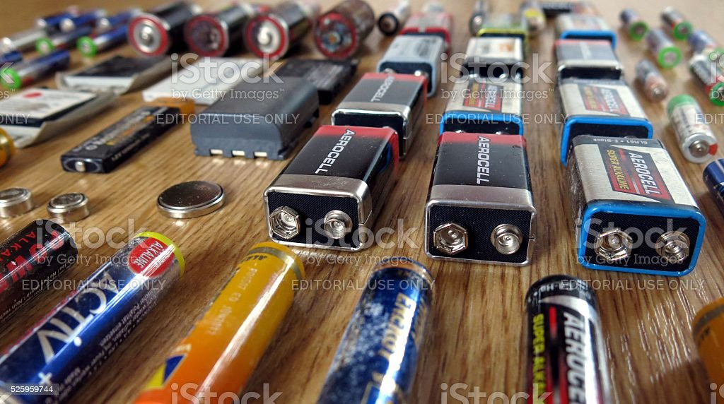 Dead batteries of different sizes arranged on wooden board stock photo