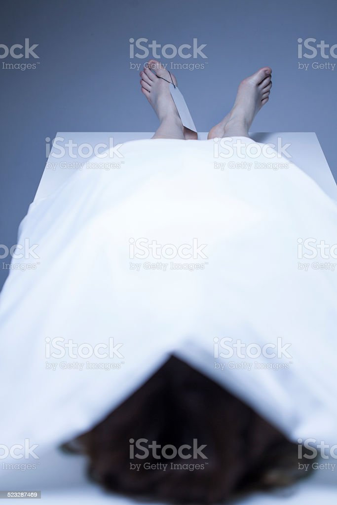 Dead body covered by sheet stock photo