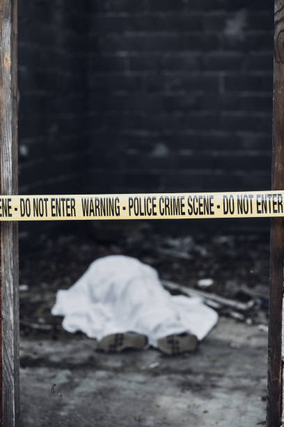 Dead body in a room that is covered by a cordon tape stock photo