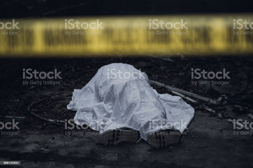 Dead body on the ground behind a cordon tape stock photo
