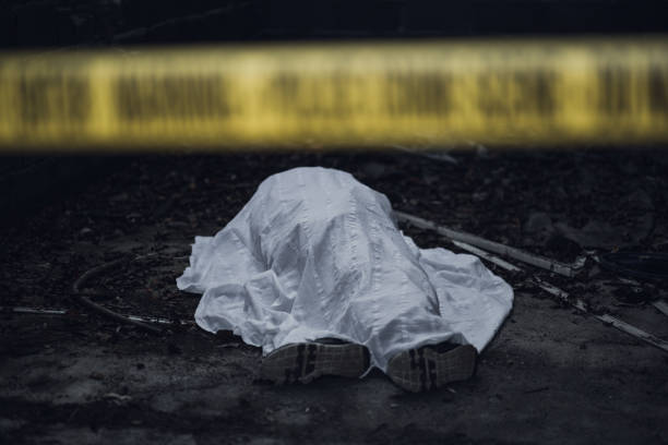 dead body on the ground behind a cordon tape - mata imagens e fotografias de stock