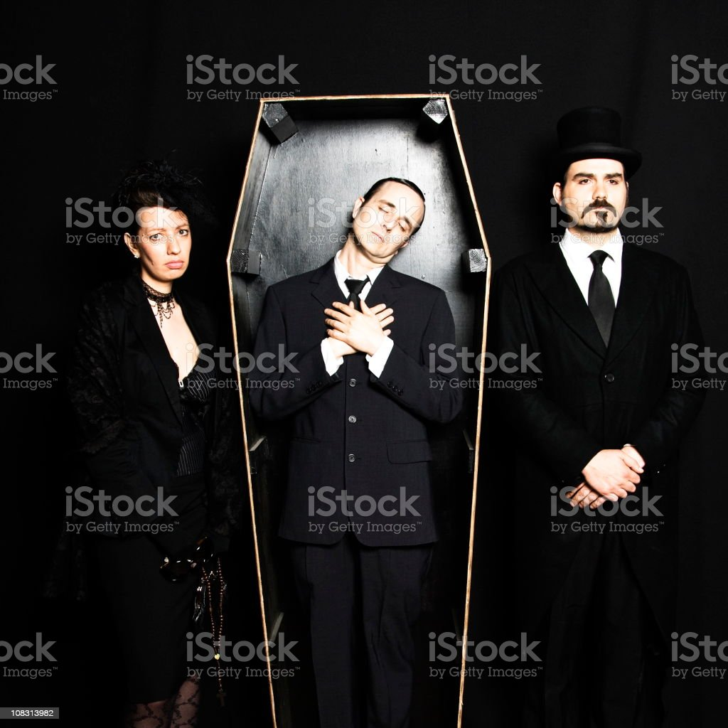 Dead husband in coffin with grieving wife and undertaker stock photo