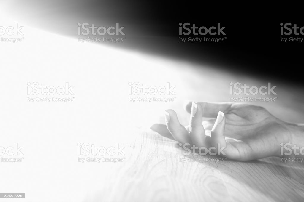 Dead or unconcscious woman's hand on floor stock photo