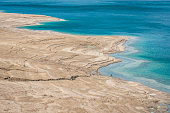 Scenic view from above along the dry rocky Dead Sea Coast of the West Bank Israel. Tourist walking down the rocky coast to swim in the salty water of the Dead Sea. Dead Sea, Ein Gedi, Israel, Middle east.