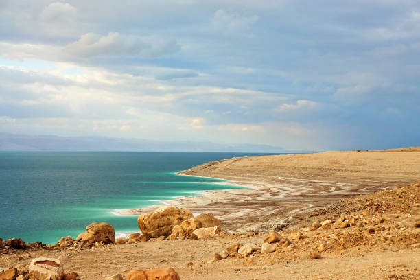 Dead sea shore at Jordan side, dry sand and rocks beach, sun shines on beautiful azure water surface stock photo