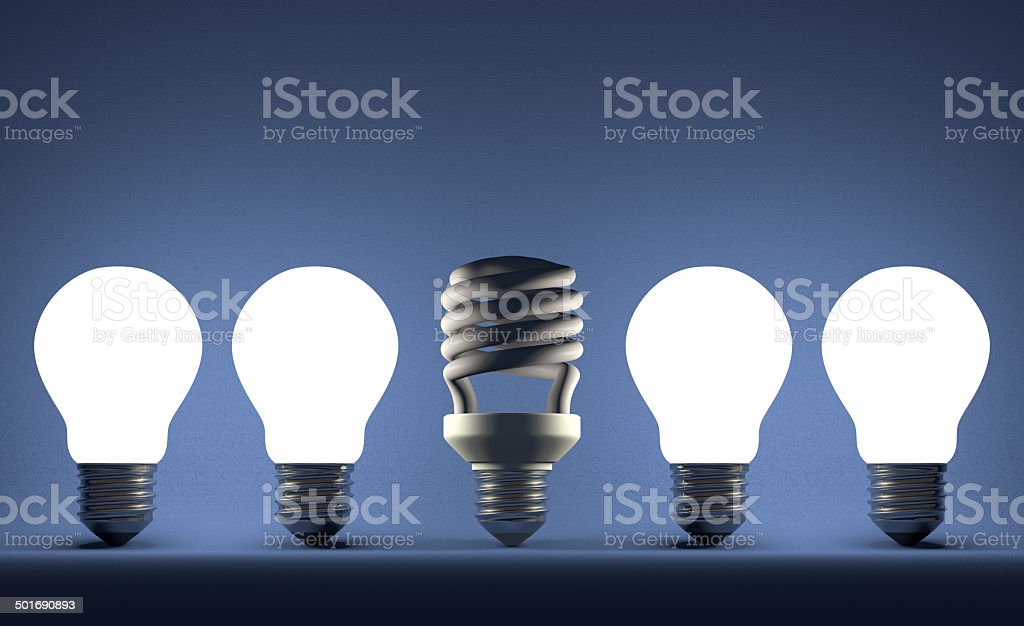 Dead spiral lightbulb among glowing tungsten ones on blue royalty-free stock photo