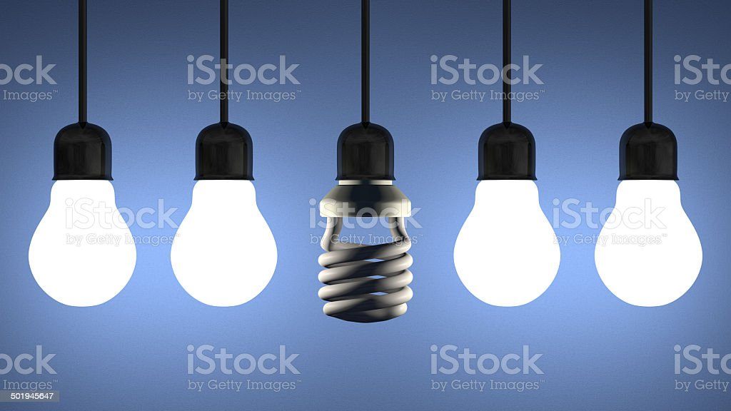 Dead spiral lightbulb hanging among glowing tungsten ones on blue stock photo