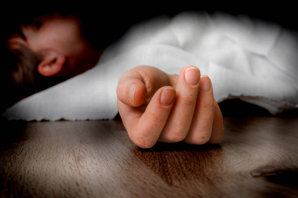 Dead woman lying on the floor under white cloth stock photo