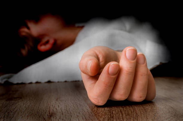 Dead woman lying on the floor under white cloth Dead woman lying on the floor under white cloth with focus on hand dead stock pictures, royalty-free photos & images