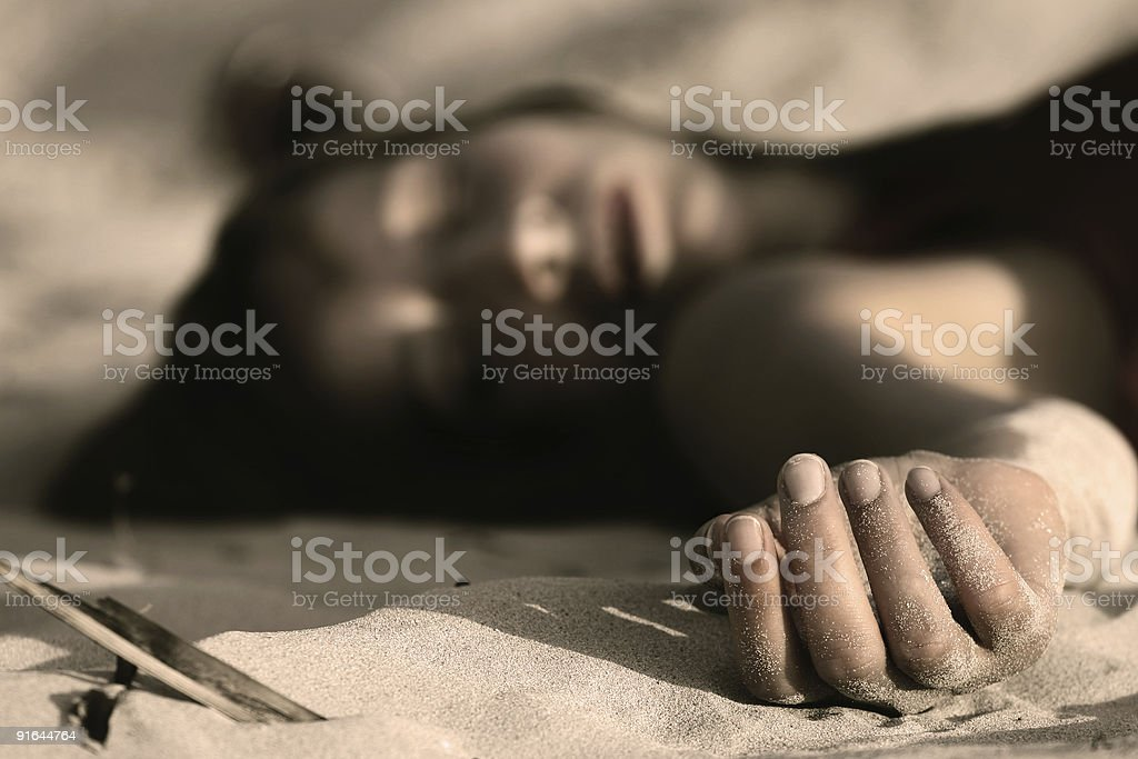dead woman on the sand stock photo