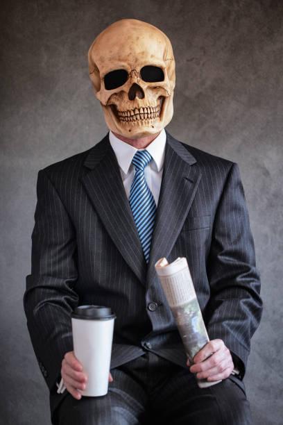 dead zombie man i marinblå kritstrecks randig kostym business suit med ljusblå slips mot en grå bakgrund bär en skrämmande mänsklig skalle mask innehar en tidning och vit kopp kaffe-bild - coffe with death bildbanksfoton och bilder