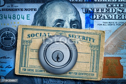 A deadbolt lock and a Social Security card rests on top of a one hundred dollar bill.