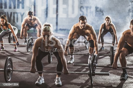 Large group of athletes exercising deadlift with barbells in a health club. Focus is on man with beard.