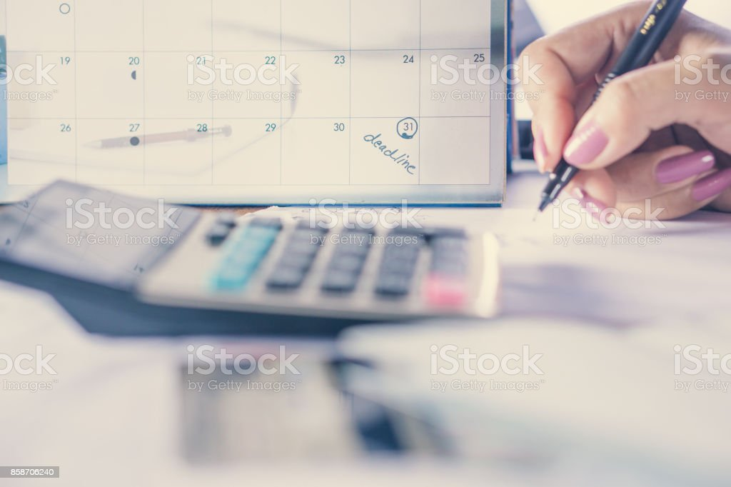 deadline calendar note with business woman hand calculating her monthly expenses with credit card, idea for shopping online stock photo