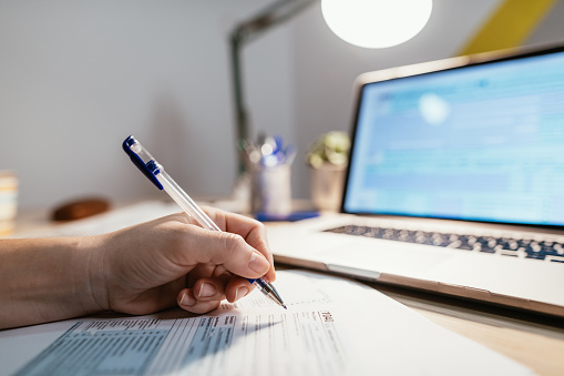 Working from home due to social distancing , woman is filling out tax form
