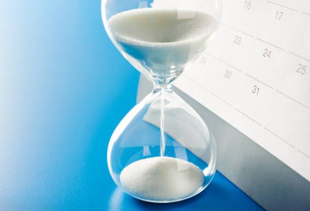 kalender mit fokus auf der ende des monats - sanduhr stock-fotos und bilder