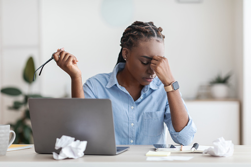 Deadline Stress. Overworked Black Female Entrepreneur Massaging Nosebridge At Workplace In Office, Exhausted After Using Laptop