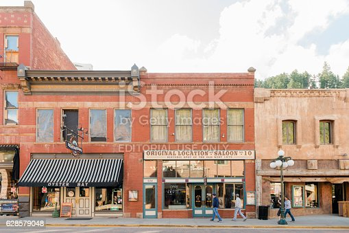 Deadwood, United States - May 8, 2016: Historic buildings in this Western South Dakota town remain active with a variety of retail businesses. People walk along the sidewalk.