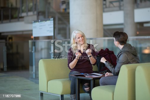 A deaf lesbian couple are communicating using sign language while seated around a table in a mall