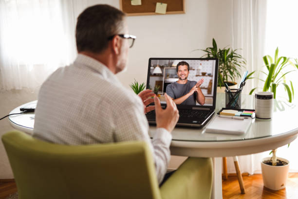 Deaf man talking using sign language on the laptop at home. Deaf man talking using sign language on the laptop at home. signing stock pictures, royalty-free photos & images