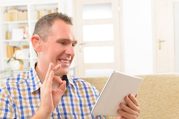 Deaf man using sign language on the tablet stock photo