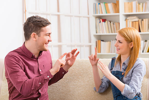 deaf man with his girlfriend using sign language - sign language stock photos and pictures