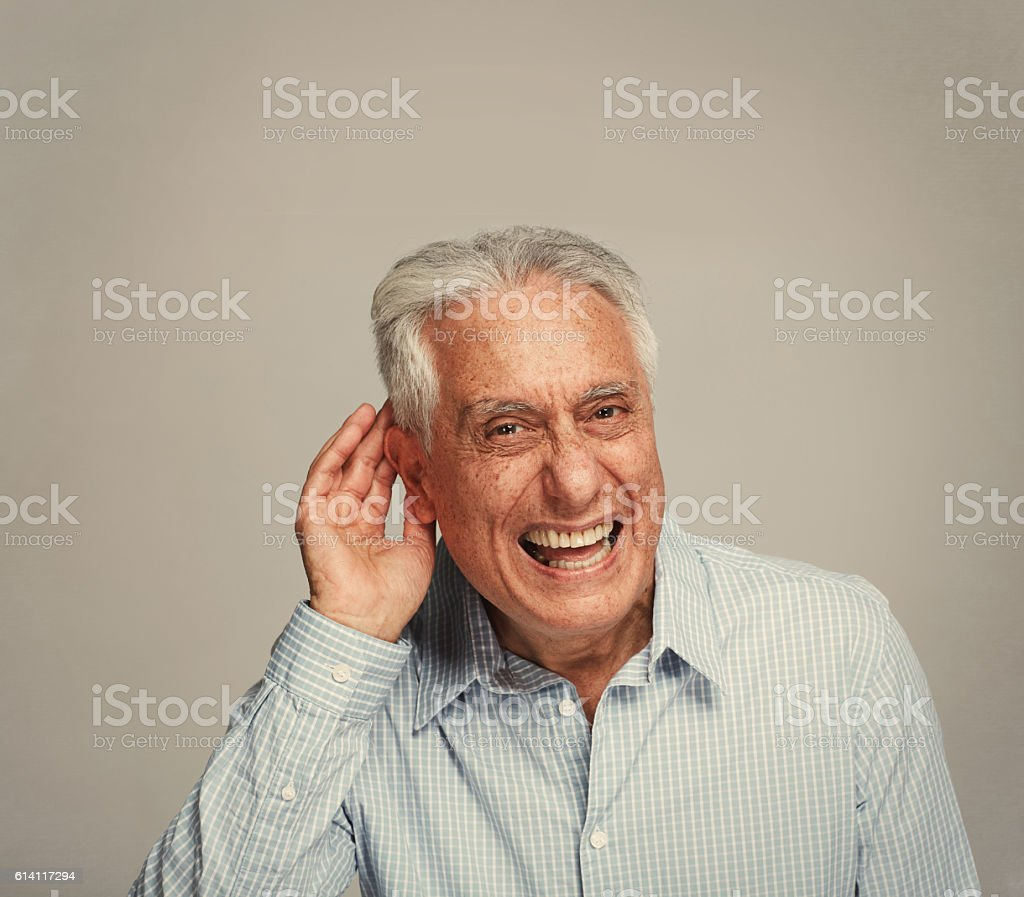 Deaf senior man holding hand near ear. – Foto