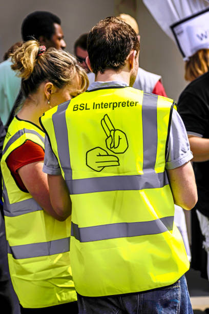 Deaf Sign language Interpreters wearing yellow jackets at the Liberty Festival London stock photo