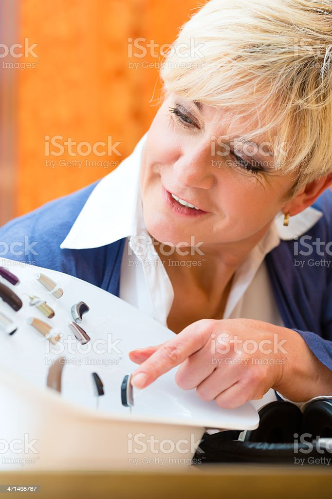 A deaf woman pointing at a hearing test royalty-free stock photo