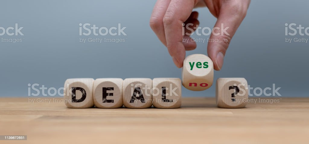 "Deal or no deal? Hand turns a cube and changes the word ""no"" to ""yes"". Deal or no deal? Hand turns a cube and changes the word ""no"" to ""yes"". Agreement Stock Photo"
