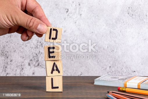 Deal. Wooden letters on the office desk. Money and pencils
